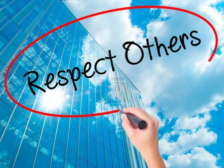 Photo for Women Hand writing Respect Others with black marker on visual screen. Isolated on skyscraper. Business, technology, internet concept. Stock Photo - Royalty Free Image