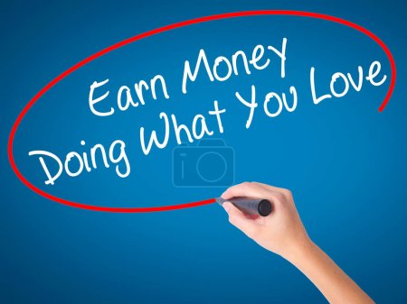 Photo for Women Hand writing Earn Money Doing What You Love with black marker on visual screen. Isolated on blue. Health, technology, internet concept. Stock Image - Royalty Free Image