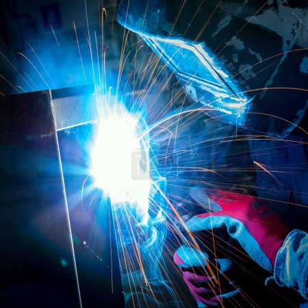 worker with plasma welding machine