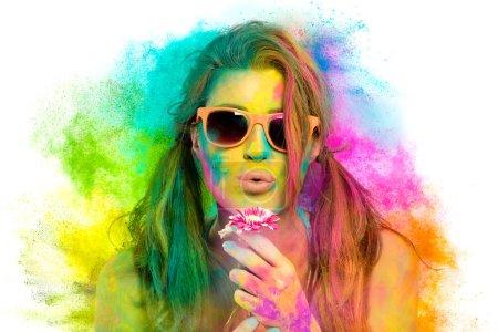 Photo pour Belle femme sensuelle couverte de poudre colorée arc-en-ciel utilisée pour célébrer le festival Holi en mars portant des lunettes de soleil colorées et du rouge à lèvres nu soufflant doucement une fleur dans un concept de printemps de beauté - image libre de droit