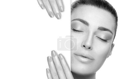 Photo pour Portrait monochrome d'une belle femme avec une peau lisse et impeccable et des ongles soignés posant les yeux fermés et une expression sereine tenant une carte blanche avec espace de copie. Beauté visage Spa Femme . - image libre de droit