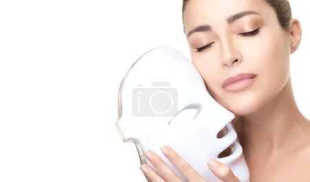 Photo pour Beauté visage femme avec masque led. Soins de la peau. Processus beauté anti-âge. Photonothérapie léger traitement rajeunissement de la peau conduit masque facial. Femme spa peau saine isolée sur bannière blanche. Espace de copie - image libre de droit
