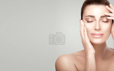 Photo pour Belle femme sereine avec une peau fraîche et propre. Femme de peau païenne tenant gracieusement ses mains sur son visage aplatissant traitement du visage. Cosmétologie, soins de beauté ou concept de soins de la peau - image libre de droit