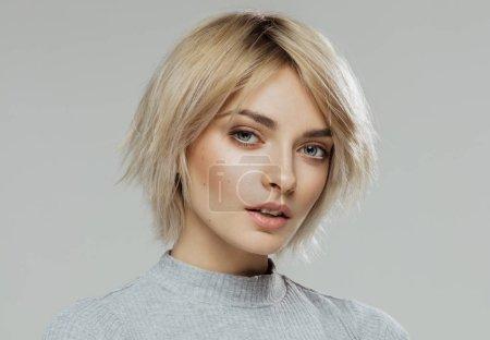 Foto de Retrato de la belleza del rostro femenino con la piel natural aislada en gris - Imagen libre de derechos