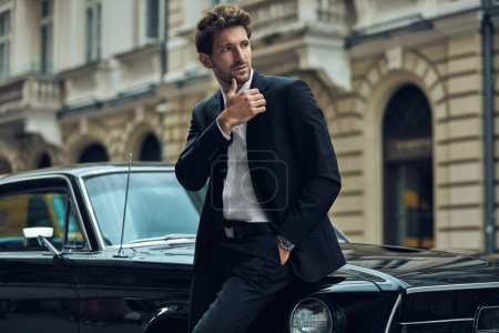 Photo for Young handsome man with black classic car wearing black suit - Royalty Free Image