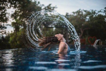 junge Frau im Freibad macht Haarspray.