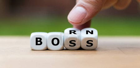 """Photo for Born to be a boss. Hand turns dice and changes the word """"BORN"""" to """"BOSS"""". - Royalty Free Image"""