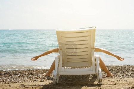 Photo for Woman is lying on the sunbed in funny pose. She is tired and enjoy her long-awaited vacation. - Royalty Free Image