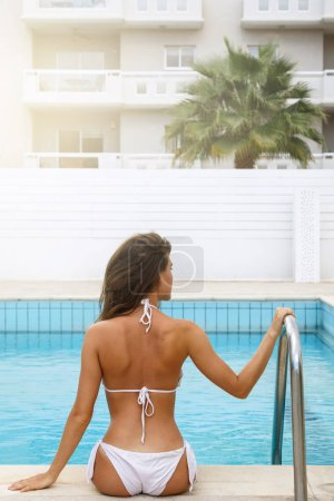 Beautiful young woman beside a swimming pool at sunny day