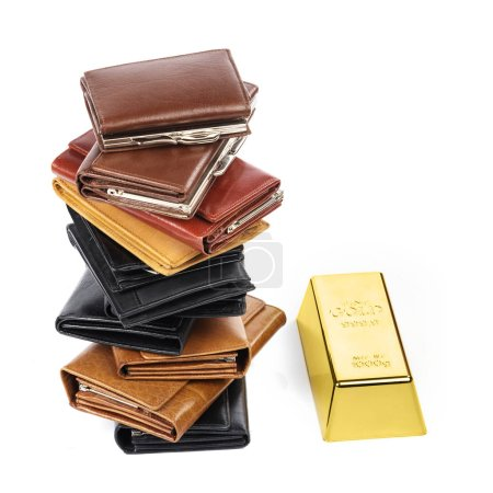 Lot of leather wallets and gold bar on white background