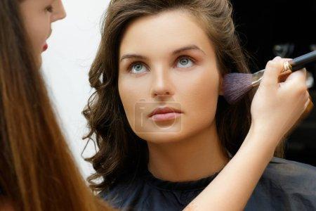 Makeup artist applying cosmetics on model face