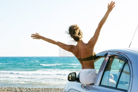 Photo for Happy and carefree woman in the car on the beach - Royalty Free Image