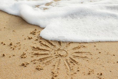 Drawing of sun on sand and wave foam
