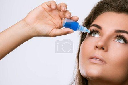 Photo pour Belle jeune femme à l'aide de gouttes pour les yeux - image libre de droit