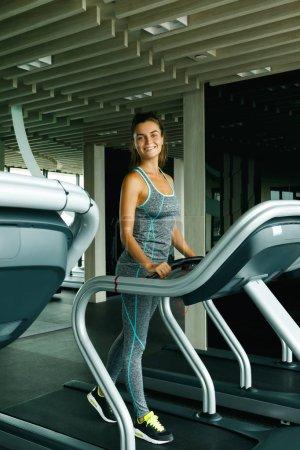 Photo pour Jeune femme sportive sur tapis roulant dans la salle de gym - image libre de droit
