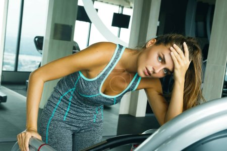 Woman on the treadmill with overtraining symptoms