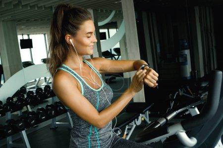 Photo pour Femme utilise montre intelligente au cours de son entraînement dans la salle de gym - image libre de droit