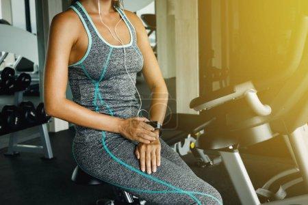 Photo pour Femme avec smart montre en vélo de staionary dans la salle de gym - image libre de droit