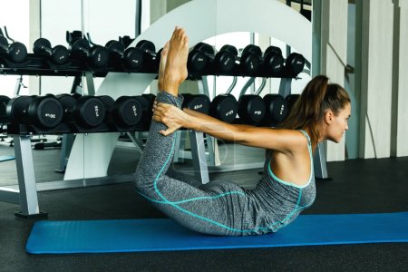 Sporty young woman doing stretching exercise in the gym