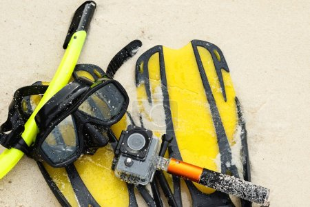 Equipment for snorkeling and action camera in waterproof case on the beach