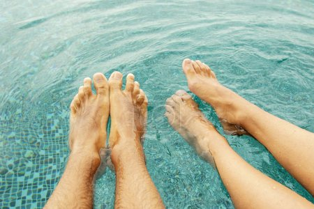 Male and female legs in the swimming pool