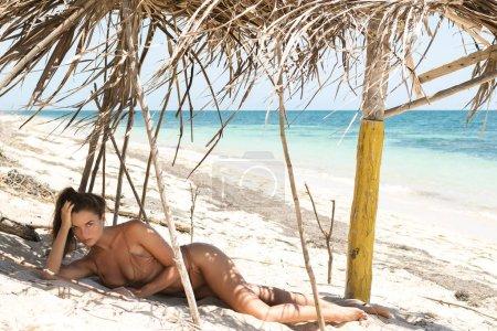 Sexy hermosa mujer en bikini beige en la playa salvaje