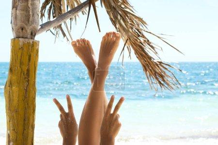 Photo pour Femme montrant le geste de paix ou de la victoire sur la plage - image libre de droit