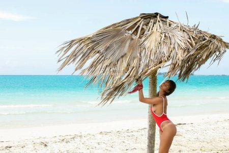 Mujer sexy en la playa de arena blanca bajo techo de paja