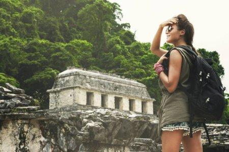 Photo pour Femme randonneuse avec sac à dos regardant d'anciennes ruines mayas - image libre de droit