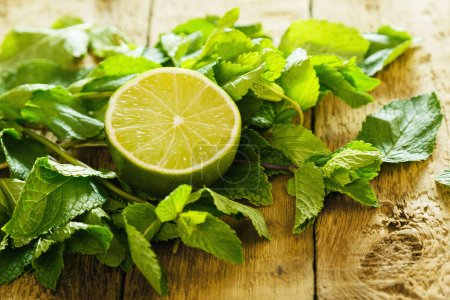 Photo for Mint leaves and half of lime on wooden table - Royalty Free Image