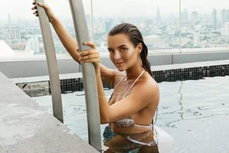 Woman relaxing on a rooftop pool with a beautiful city view on background