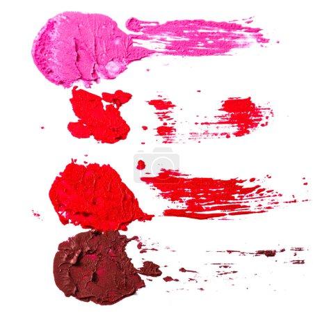 Photo pour Différents échantillons multicolores d'un rouge à lèvres maculé sur fond blanc - image libre de droit
