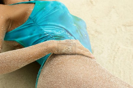 Sexy female hips covered with a sand on beach