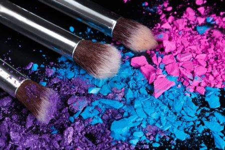 Crushed eyeshadows and make-up brushes on dark background