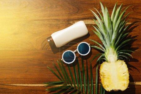 Photo pour Différents éléments pour des vacances de plage. Crème solaire, lunettes de soleil et ananas fruits - image libre de droit