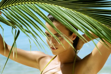 Photo for Portrait of beautiful woman with shadows of palm leaf on her face - Royalty Free Image