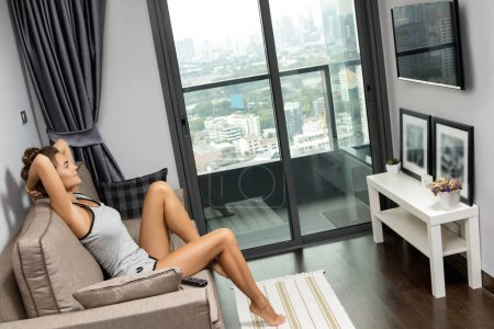 Woman sitting on couch and watching TV in modern apartment