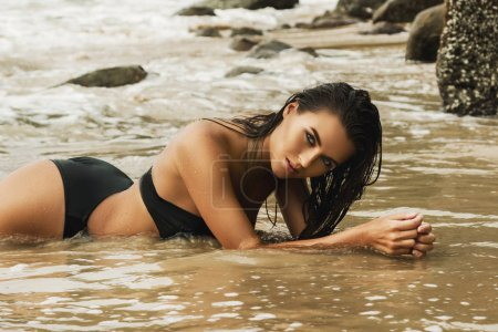 Photo for Sexy beautiful woman posing on wet sand on the beach - Royalty Free Image