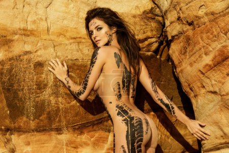 Photo for Beautiful naked woman with trace of car tire on her body is posing beside the sand cliffs - Royalty Free Image