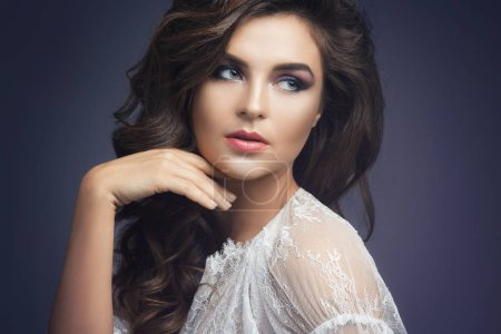 Portrait of young woman in white dress with beautiful makeup and hairstyle