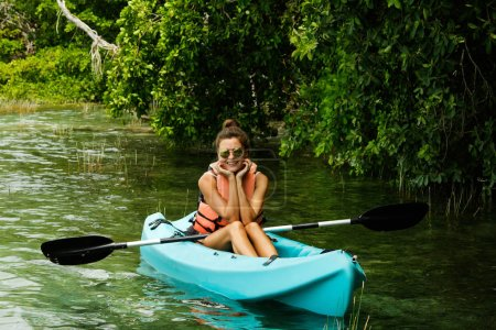 Happy young beautiful woman kayaking in on the lake