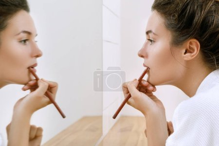 Photo for Woman drawing lip contour with a pencil - Royalty Free Image