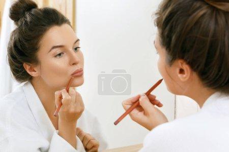 Photo pour Femme dessin contour des lèvres avec un crayon - image libre de droit