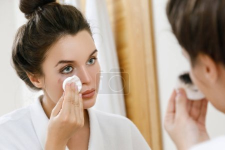 Young woman removing makeup with a cotton pad
