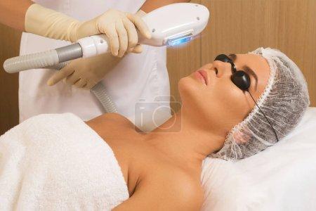 Beautiful woman in professional  beauty salon during photo rejuvenation procedure