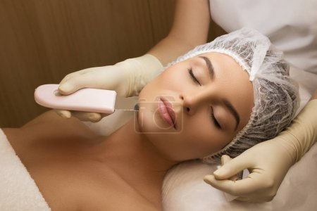 Beautiful woman in professional beauty spa salon during ultrasonic facial cleansing procedure