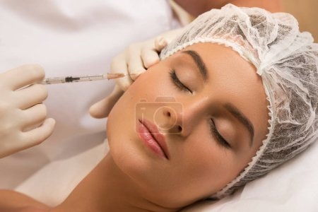 Woman in professional beauty salon during facial injections for rejuvenation