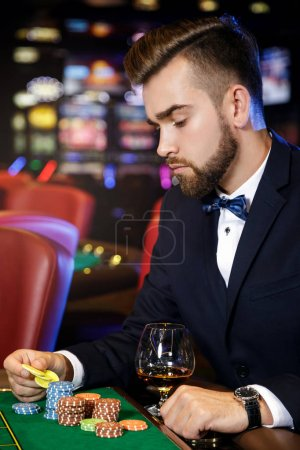 Rich handsome man playing roulette in the casino