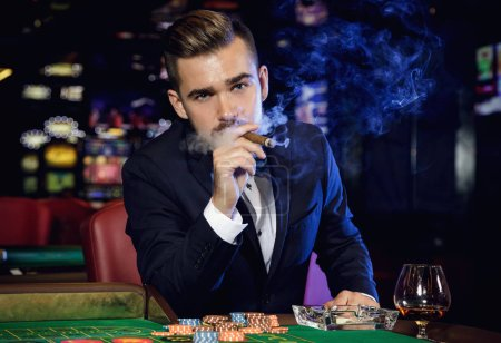 Photo pour Riche bel homme fumant du cigare et jouant à la roulette au casino - image libre de droit