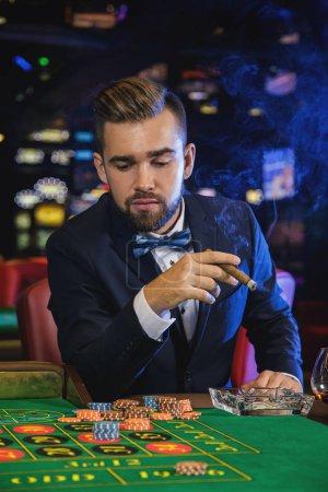 Photo pour L'homme riche beau cigare fumer et jouer à la roulette au casino - image libre de droit